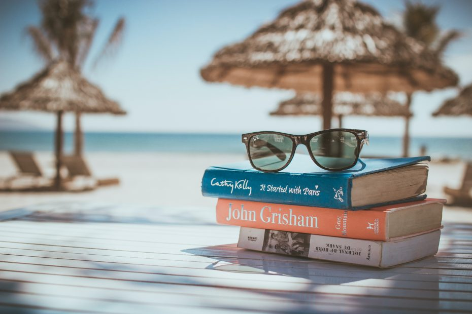 sunglass on stack of books on table in the tropics